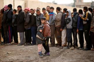 伊拉克摩蘇爾以東一個聯合國的救濟站門外,民眾排隊領取救濟物資。