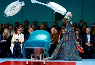 Female model in a brightly coloured dress and headscarf walks down the catwalk next to a medical bed as an audience looks on