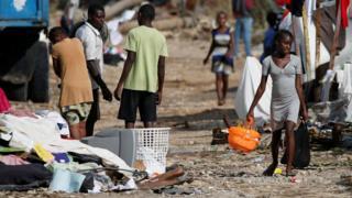 Una adolescente camina por una calle de Haití sosteniendo una cesta plástica y a su alrededor hay escombros y ropa tirada.
