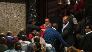 """South African opposition party Economic Freedom Fighters MP Godrich Gardee (C, in red) is evicted with fellow EFF members during the South African president""""s budget speech at the South African parliament in Cape Town on May 4, 2016."""