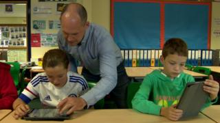 Jeffrey Dodds works with Jolene and Matthew in the classroom