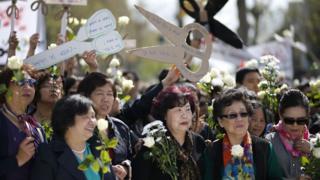 巴黎共和国广场悼念刘少尧集会现场一群妇女举起剪刀形标语牌(2/4/2017)
