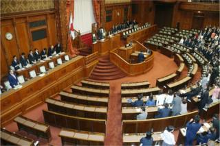 Ruling coalition lawmakers stand to accept the anti-terror law at the upper house of parliament in Tokyo on 15 June 2017.