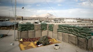 An Afghan National Army (ANA) soldier prays on the rooftop of the Musa Qala District centre base in Helmand province