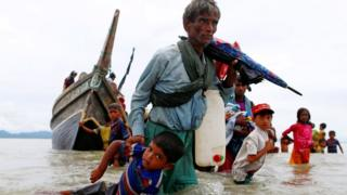 A Rohingya refugee man pulls a child as they walk to the shore after crossing the Bangladesh-Myanmar border by boat through the Bay of Bengal in Shah Porir Dwip, Bangladesh, 10 September 2017