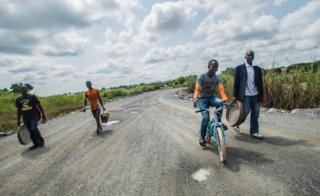 A group of men walk and cycle along a road with their equipment