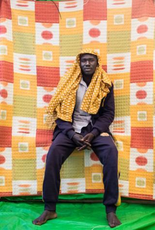 Abubaker Halin, Sudan sits with bare feet