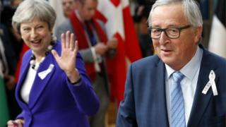 Theresa May waves at Jean-Claude Juncker