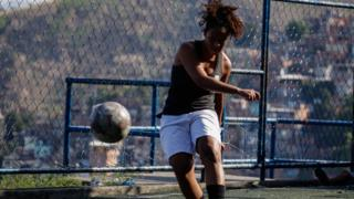 Laryssa balances on one foot at the end of her strike on goal, as the ball floats closer to the camera