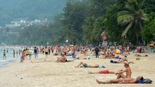 Foreign tourists relax at Patong beach in Thailand's Phuket province