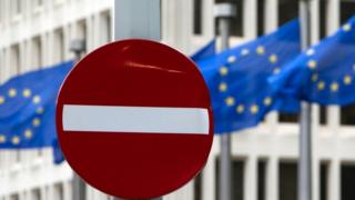 EU flags flutter in the wind in back of a no entry street sign in front of EU headquarters in Brussels on Friday, June 24, 2016.