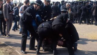 Policemen wrestling a striking miner to the ground