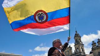 Un hombre con una bandera de Colombia con dos franjas más, una arriba y una abajo, de color blanco, símbolo universal de la paz.