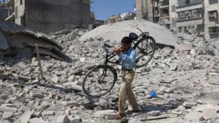 Hombre lleva una bicicleta en sus hombros tras un bombardeo en Alepo.