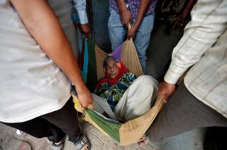 An elderly woman is carried in a blanket in Ahmedabad, India.
