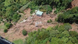A house between uprooted trees and a precipice