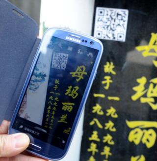 A two-dimensional quick response barcode (QR code) is affixed to a tombstone to offer smartphone users extended information about the person buried beneath on 4 April 2013 in Shenyang, Liaoning Province of China.