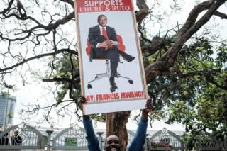 """A supporter holds a banner bearing a picture of President Uhuru Kenyatta as they celebrate on November 20, 2017 in Nairobi after Kenya""""s Supreme Court dismissed two petitions to overturn the country""""s October 26 presidential election re-run, validating the poll victory of Kenyatta."""