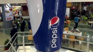 People walk past a mock giant cup of soda, part of a publicity campaign of Pepsi, at a shopping mall in Caracas on 20 December, 2015.