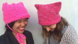 Pussyhat Project co-founders Krista Suh and Jayna Zweiman are seen laughing - wearing their hats