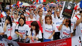 Members of the Chinese community in Paris wave French flags and hold placards during a demonstration on September 4, 2016 in Paris, following the death of Zhang Chaolin and also calling for greater security measures.