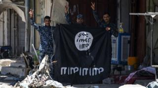Iraqi government forces flash victory signs while holding an Islamic State (IS) group flag in western Mosul on 9 June 2017