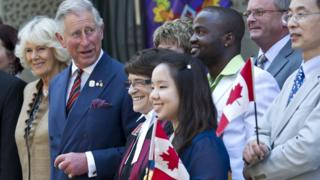 Prince Charles and his wife Camilla pose for a photograph with newly sworn in Canadian citizens following a swearing-in ceremony in Saint John, New Brunswick