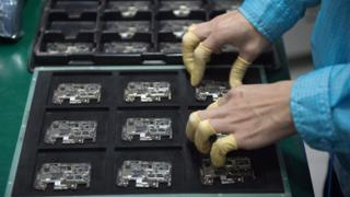 A worker checks chip component circuits at a factory in China