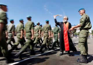 A priest sprays water as troops walk by