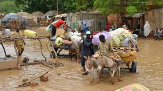 Des résidents d'un quartier de Niamey inondé évacuent leurs bagages
