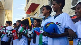 Palestinian boys dressed in football kit and carrying balls (12 October 2016)