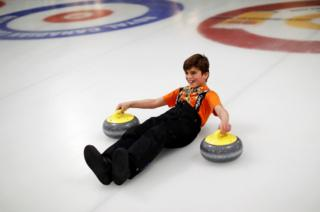 A Yazidi refugee from Kurdistan laughs as he learns the sport of curling at the Royal Canadian Curling Club during an event put on by the Together Project, in Toronto, 15 March 2017.