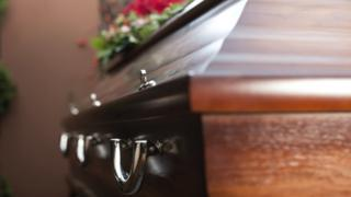 Close-up of a closed coffin and funeral flowers