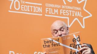 Man looking at Edinburgh International Film Festival brochure
