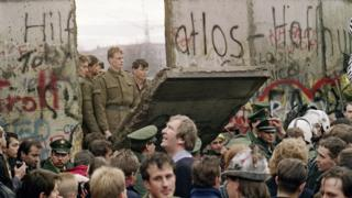 West Berliners crowd in front of the Berlin Wall early 11 November 1989 as they watch East German border guards demolishing a section of the wall.