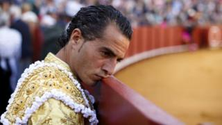 Spanish matador Ivan Fandino leans his face on the barrier during a bullfight at the Maestranza bullring in the Andalusian capital of Seville, southern Spain April 26, 2015