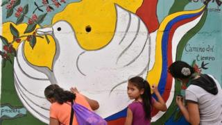 Women and a girl paint a mural alluding to peace on the road leading to Planadas, Tolima department, Colombia (August 26, 2016)