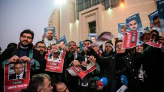 Lawyers tear into pieces pictures of accused ex-Israeli army officers as families (back) hold pictures of victims on 9 December 2016 outside the Istanbul courthouse as Turkish court is expected to rule in the case of Israelis charged in absentia over a deadly commando raid on a Gaza-bound aid ship in 2010.