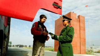 A police officer (R) checks a passport in Xinjiang (File picture October 2005)
