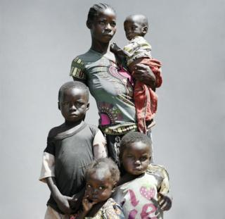 A woman stands with her four children.