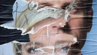 Torn and overlapping official posters of candidates for the 2017 French presidential election, Marine Le Pen and Emmanuel Macron, are seen in Cambrai, France (May 4, 2017)
