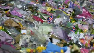 Flowers lie outside Westminster Palace in London