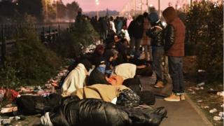 移転先を登録する窓口の前で夜を過ごした移民たち(27日)