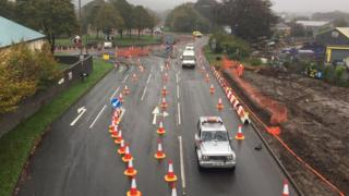 Cars driving through lanes off the roundabout lined with traffic cones