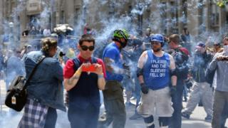 有人向游行队伍施放爆竹。