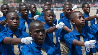 Some of students wey dey go free school for Ghana do march-past for dia Independence day