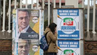 A woman walks past electoral posters of the 5 Stars candidate Luigi Di Maio and the Forza Italia party in Pomigliano D'Arco, near Naples, Italy, February 21, 2018