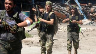 Ramuseh'de isyancılar ellerinde silahlarla sokakta yürüyor.