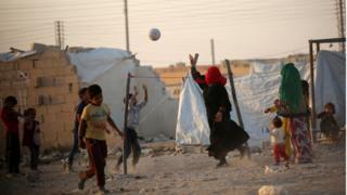 Беженцы играют в волейбол в сирийском палаточном лагере