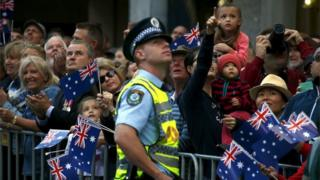 A policeman and members of the crowd look up as Royal Australian Air Force (RAAF) fighter jets fly overhead during the ANZAC (Australian and New Zealand Army Corp) Day march through central Sydney, Australia, April 25, 2016